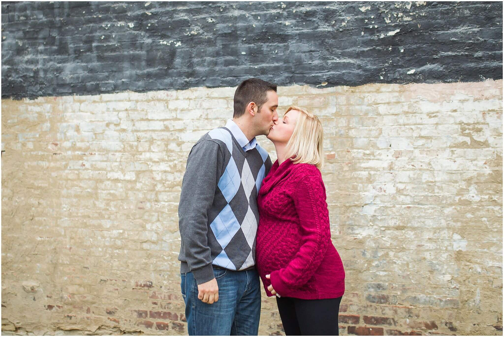 pittsburgh maternity portrait session jaclyn and thomas, kissing in front of a tall brick wall in pittsburgh.